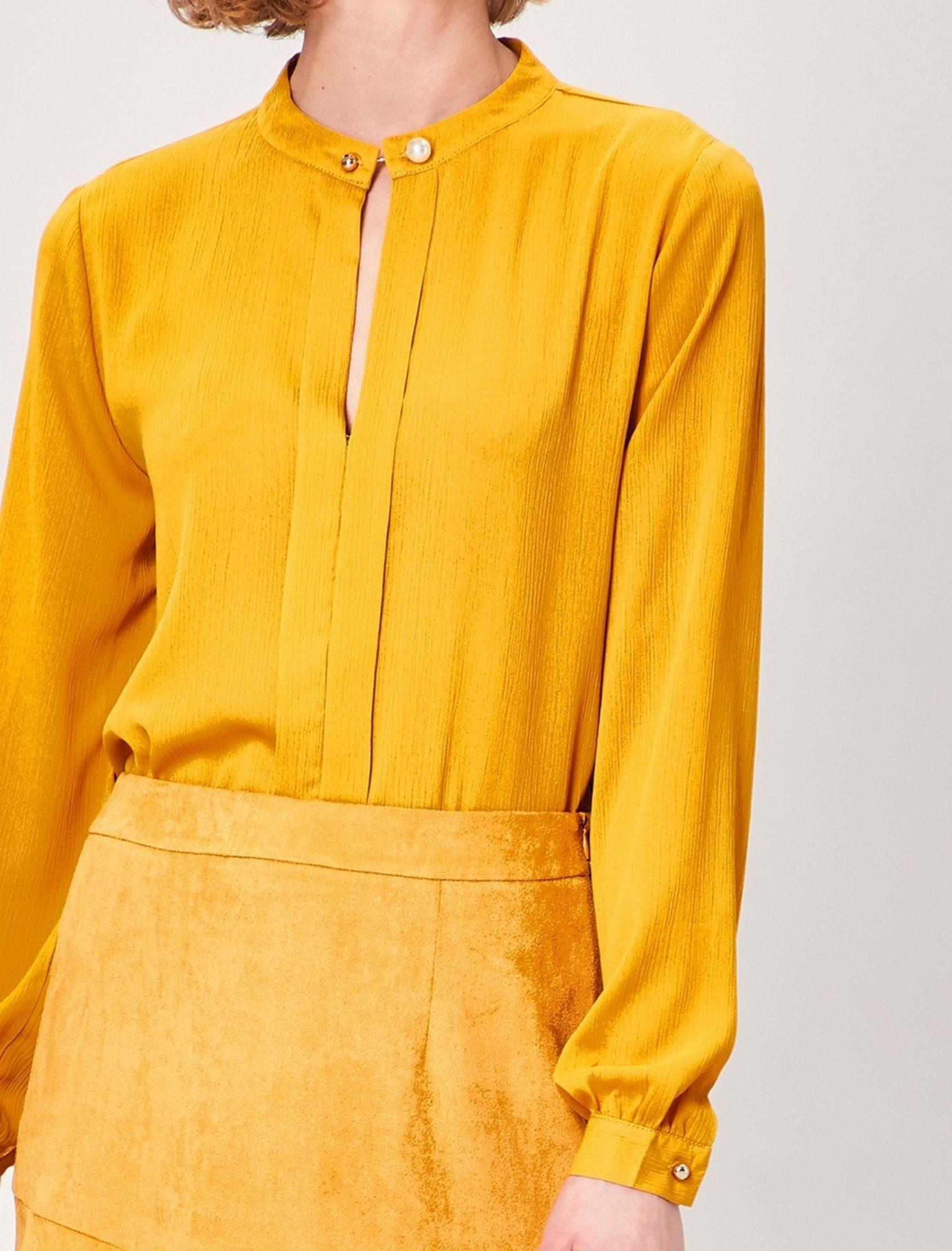blusa de mujer en tono mostazo con detalle de alfiler de la marca angeleye