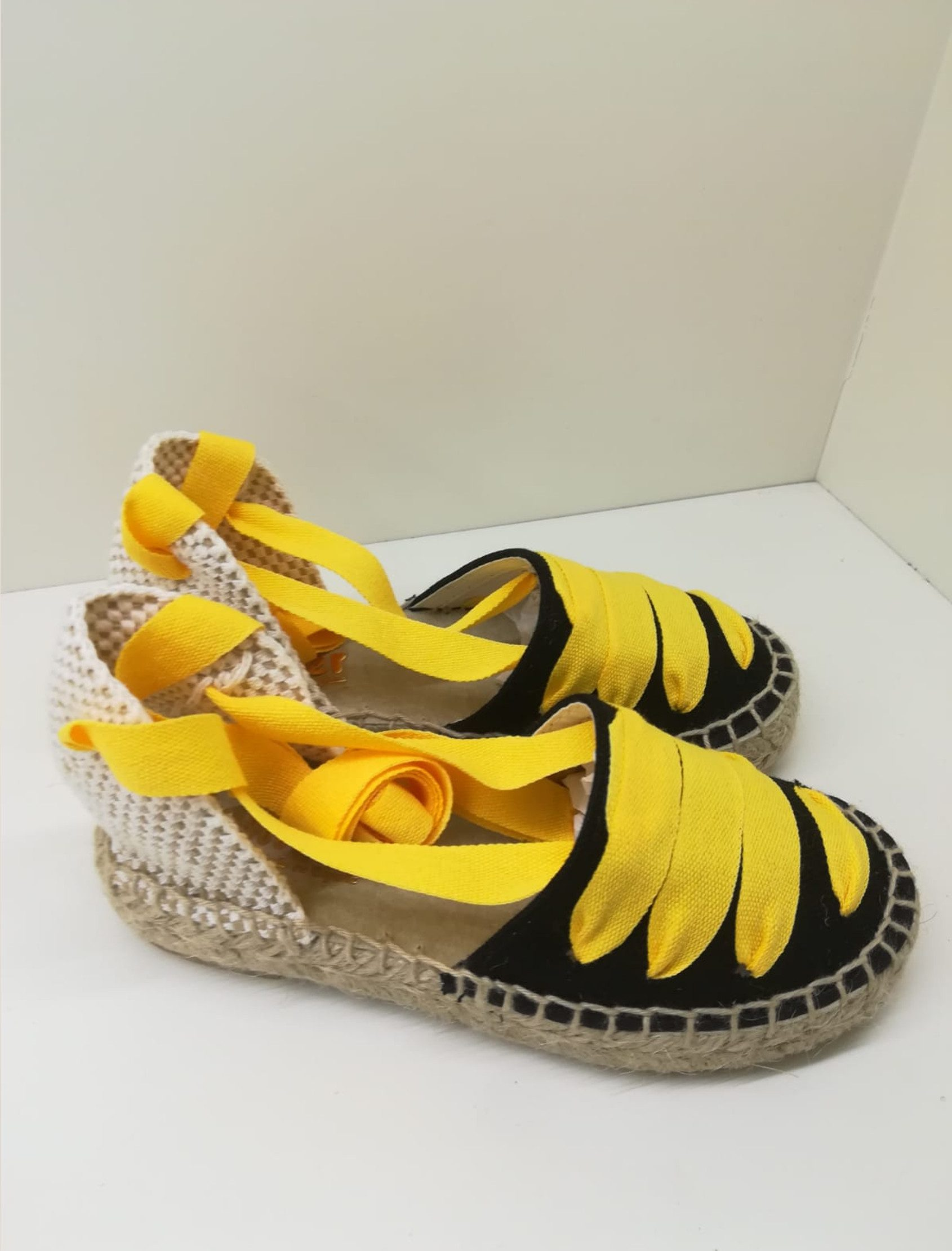Alpargata negra combinada con lazos en amarillo que atan a la pierna. Plantilla totalmente en piel.