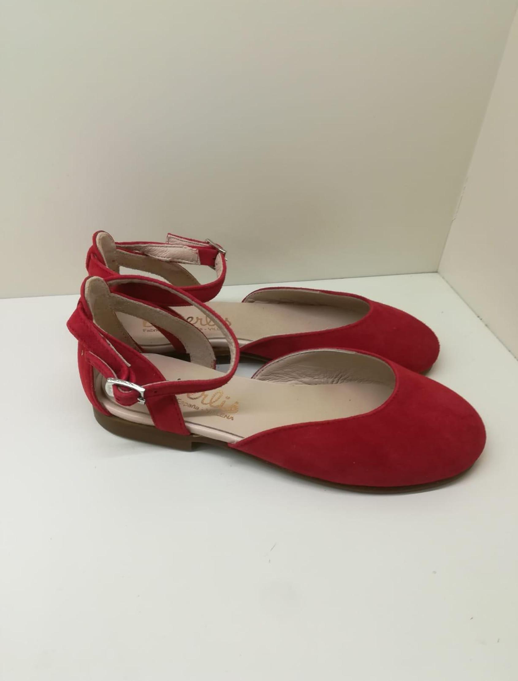 Merceditas en ante rojo semiabierta con correa y hebilla para cierre en el tobillo.