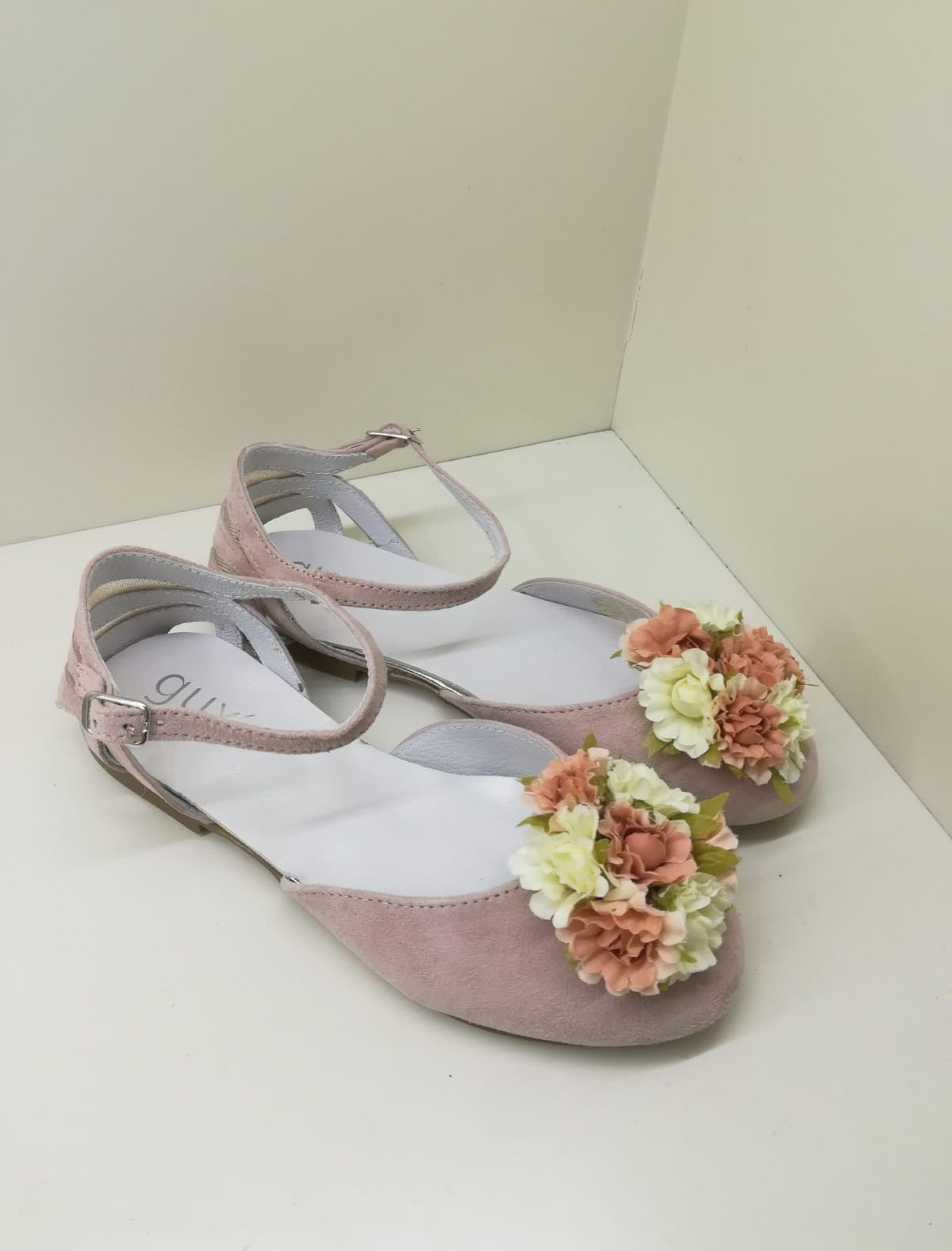 """Bailarina en ante rosa empolvado, semiabierta y detalle con """"pompón"""" de flor delante. Aberturas en el talón. Ajustable con correa al tobillo y hebilla."""