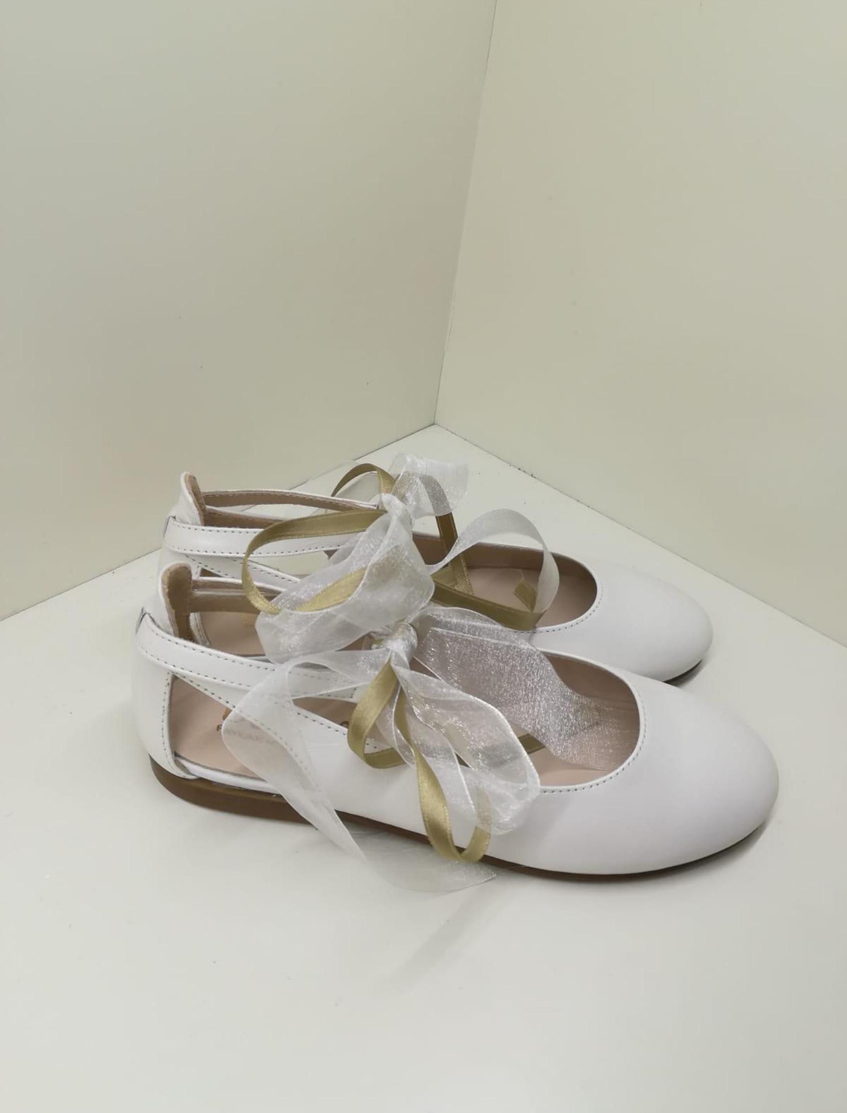 Bailarina Siria Bone en color blanco roto.Con correa con cierre de hebilla y correa con lazos que le da más elegancia a esta preciosa bailarina.
