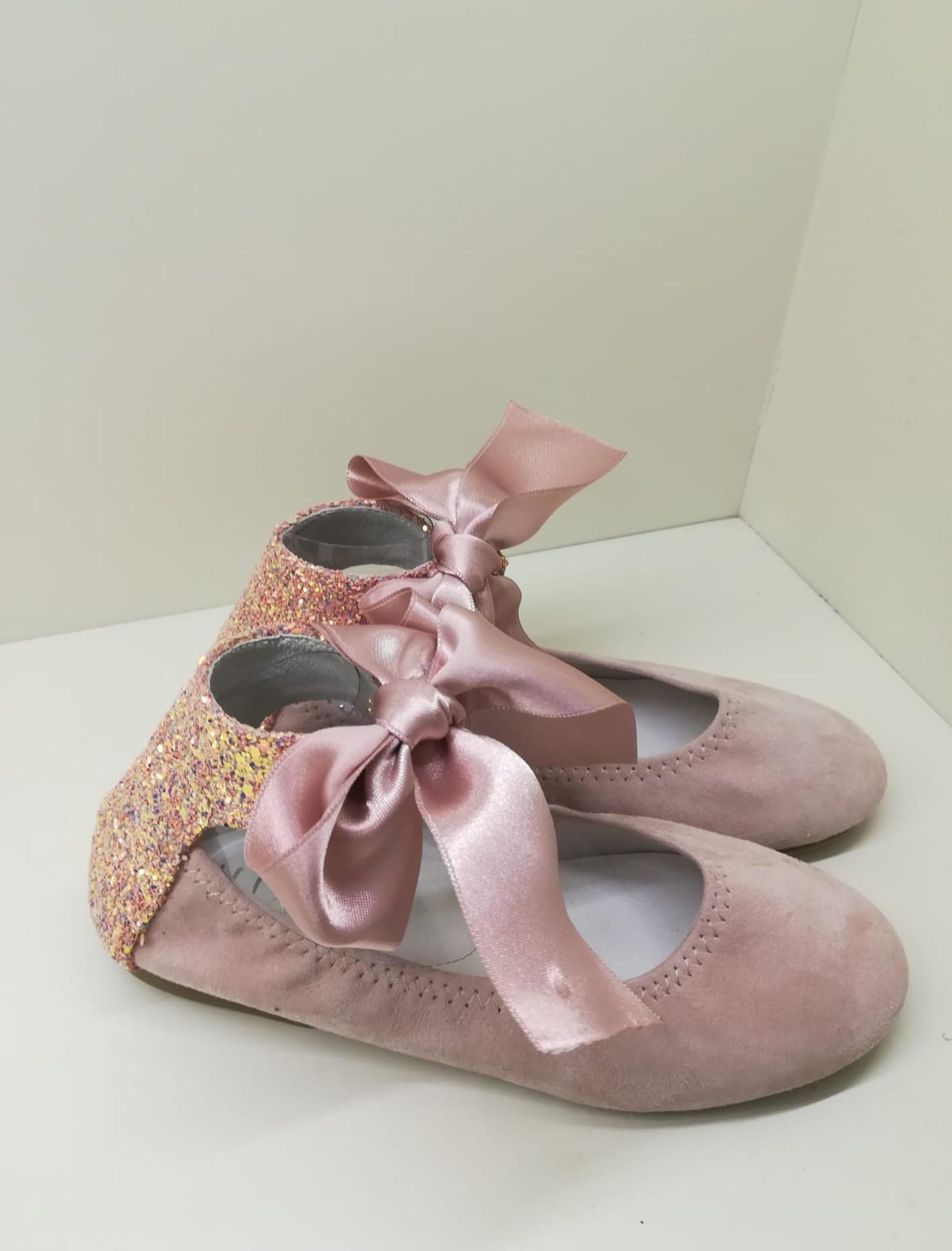 Bailarina en ante rosa con trasera en glitter rosa. Ata al tobillo con lazo ancho de raso.