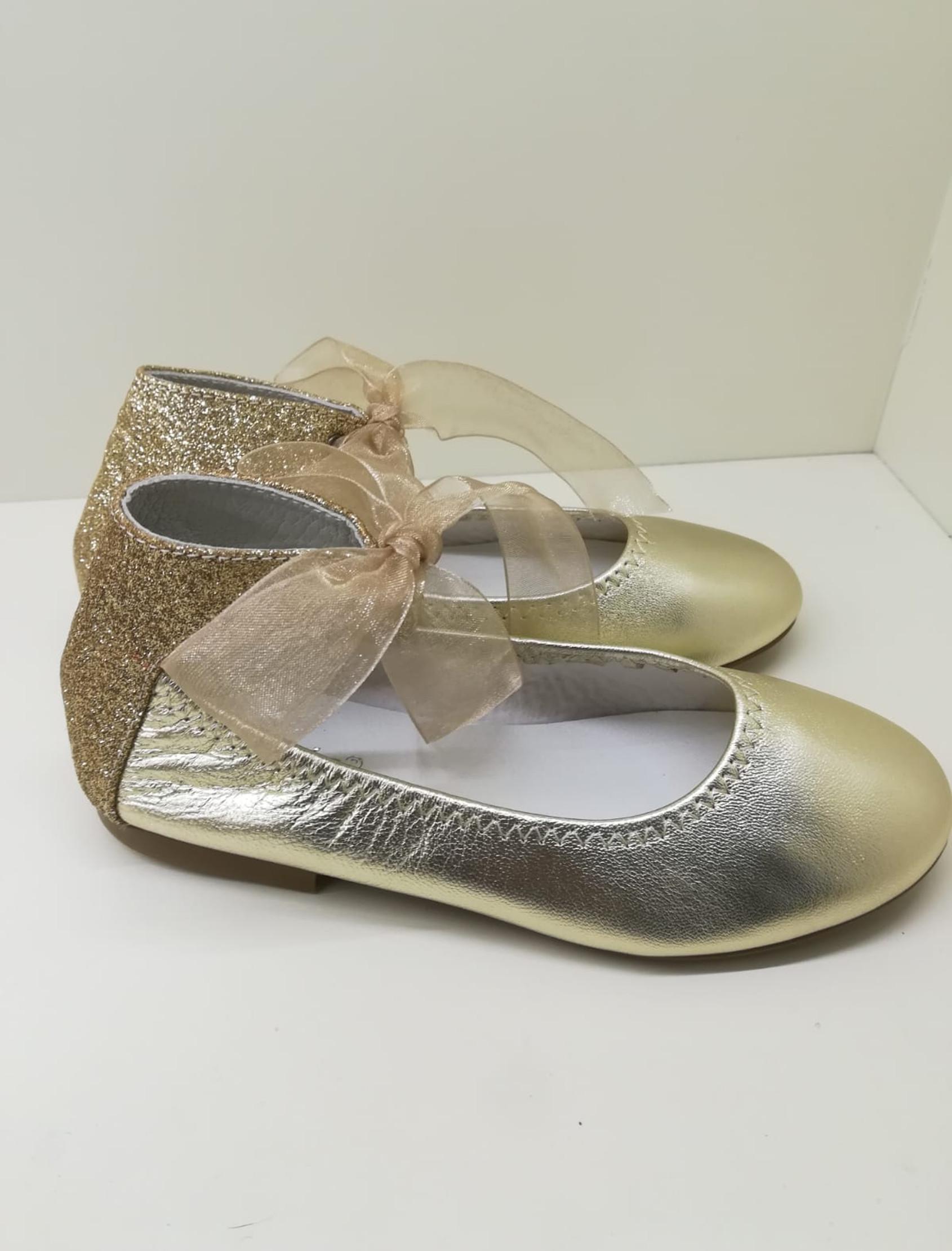 Bailarina en laminado oro con trasera en glitter oro. Ata al tobillo con lazo de organza.