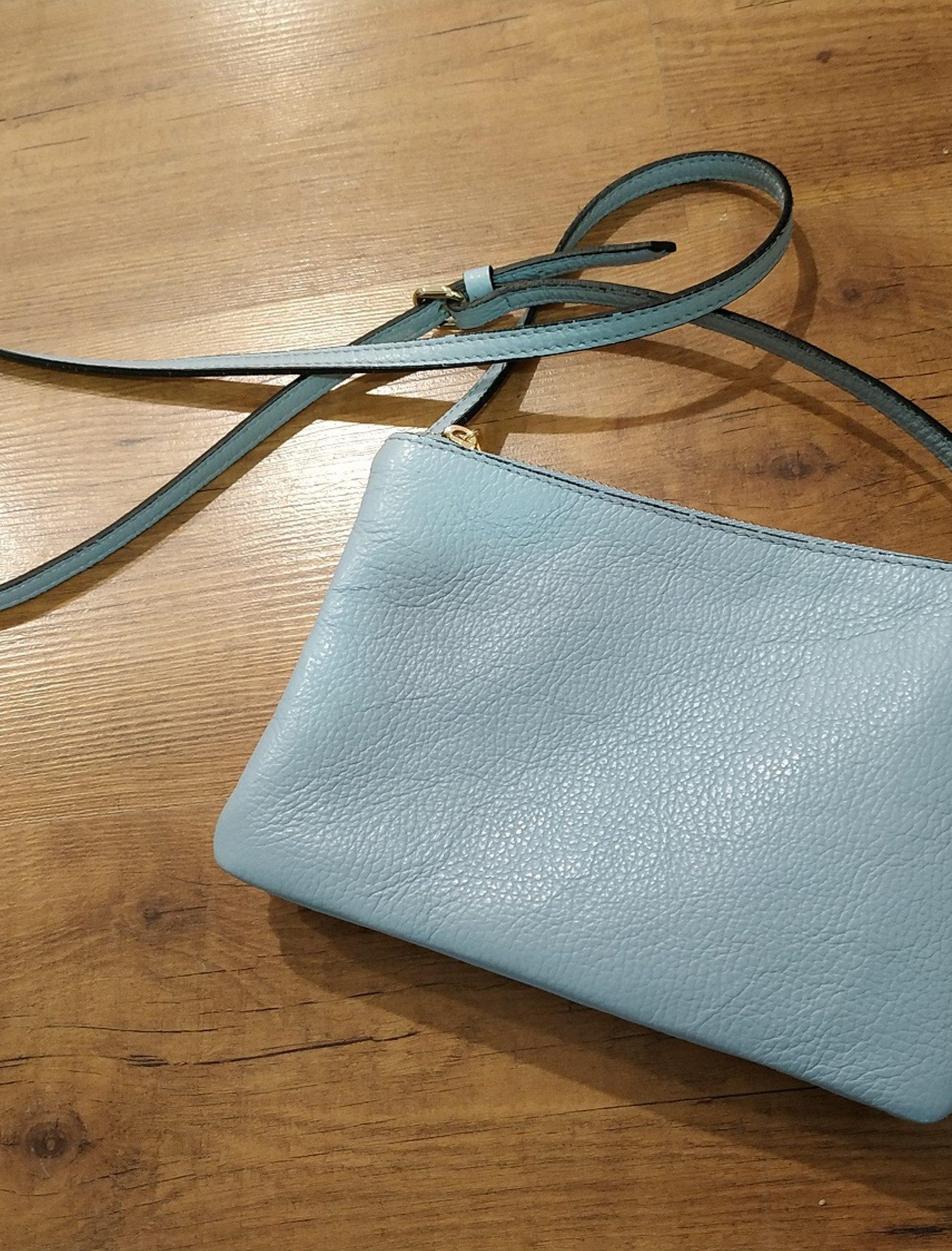 Bolso bandolera de largo regulable de piel. El bolso se ha confeccionado con tres estuches con cremallera que se fijan mediante botones a presión.