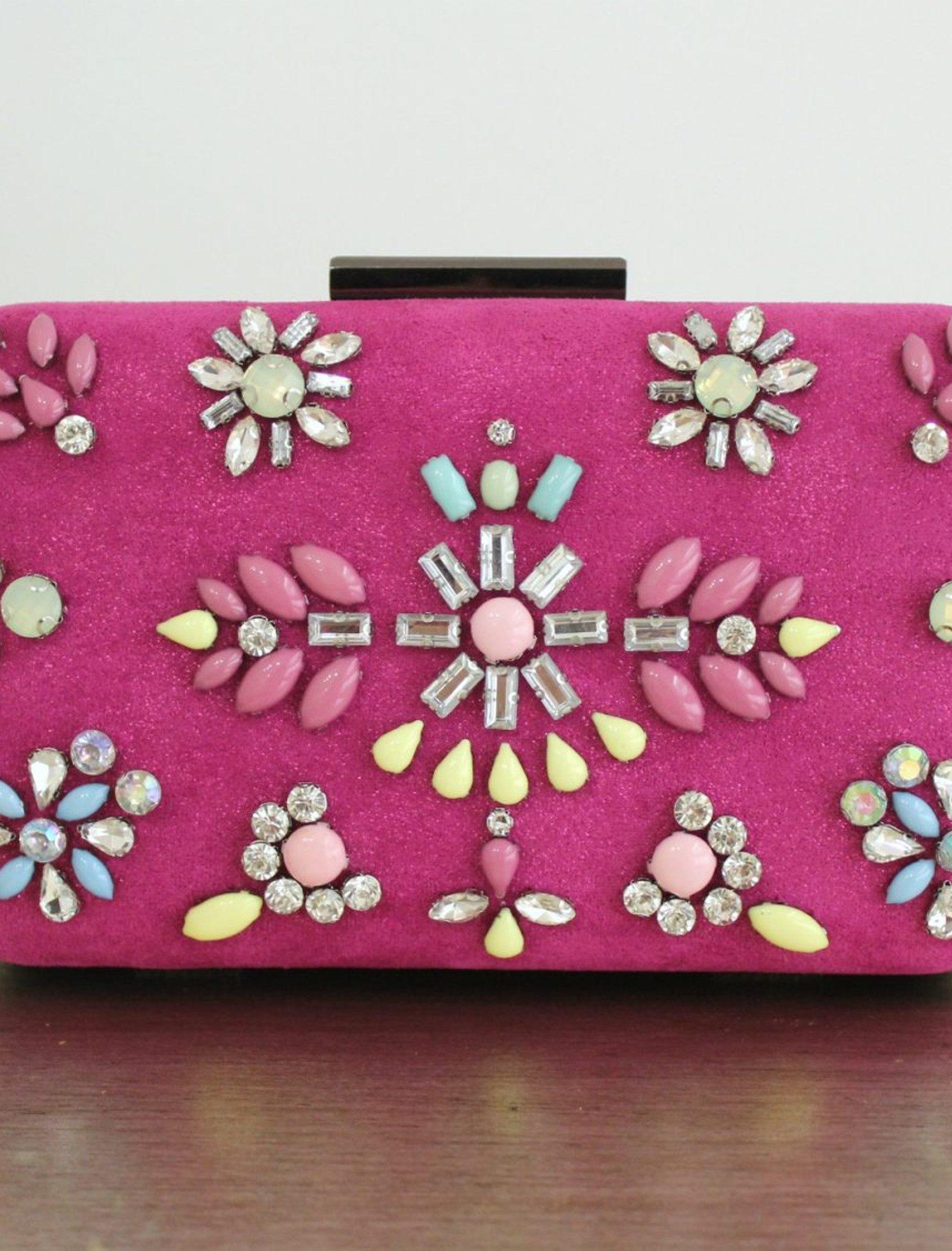 Clutch confeccionado en antelina irisada, esta cartera lleva pedrería multicolor en colores empolvados. Dispone de cadena metálica y cierre a presión.