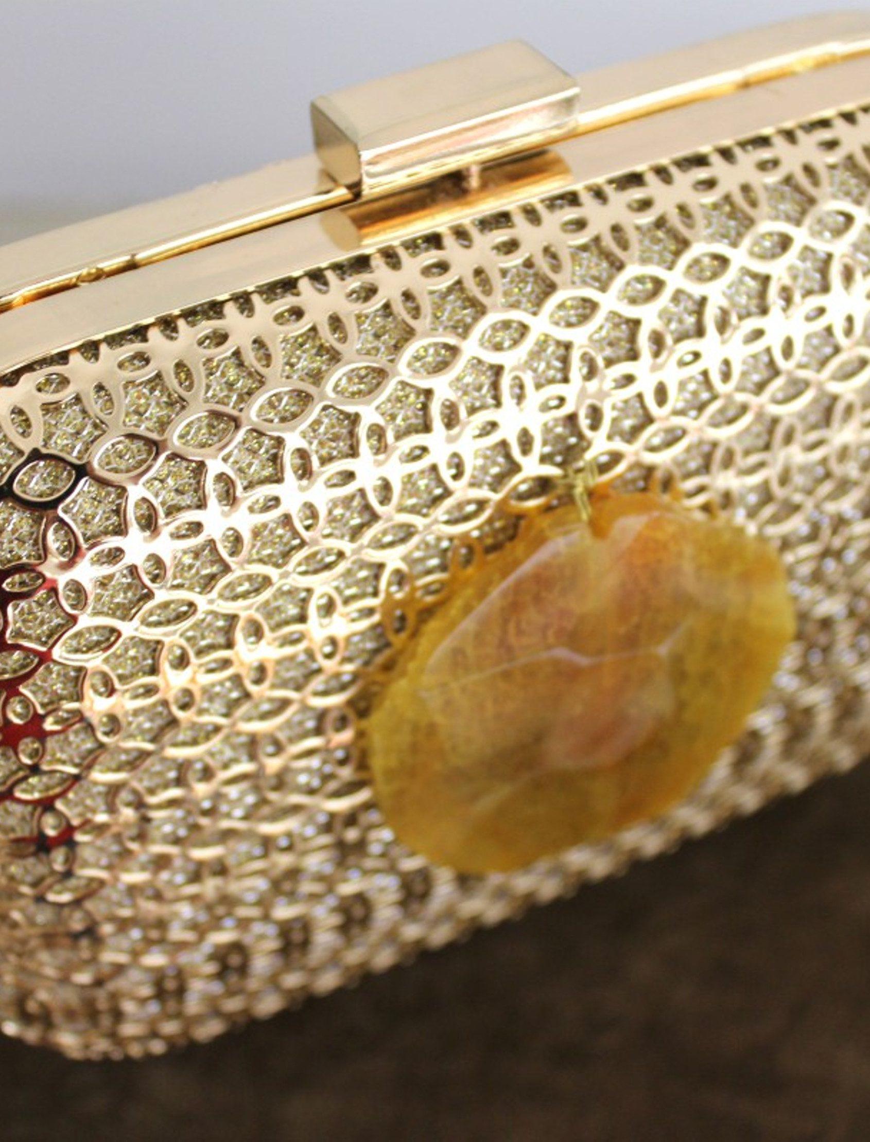 Clutch Geoda de cuerpo metálico calado en color oro claro, con una piedra engarzada en medio.La piedra va unida con hilo metálico.