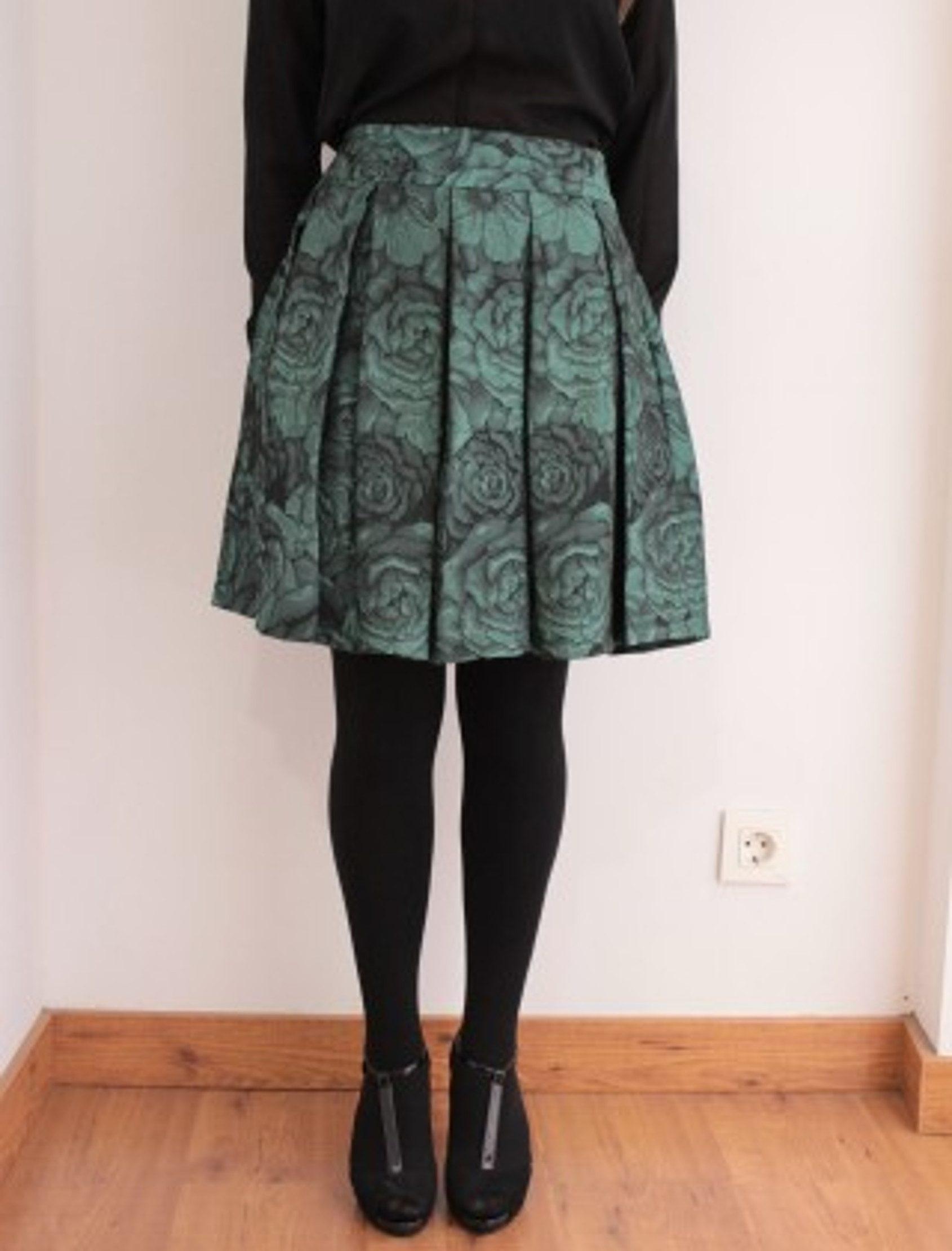 Falda de largo medio, por encima de la rodilla, en un tejido brocado, de poco relieve con una combinación de verde y negro con un poco de brilo.