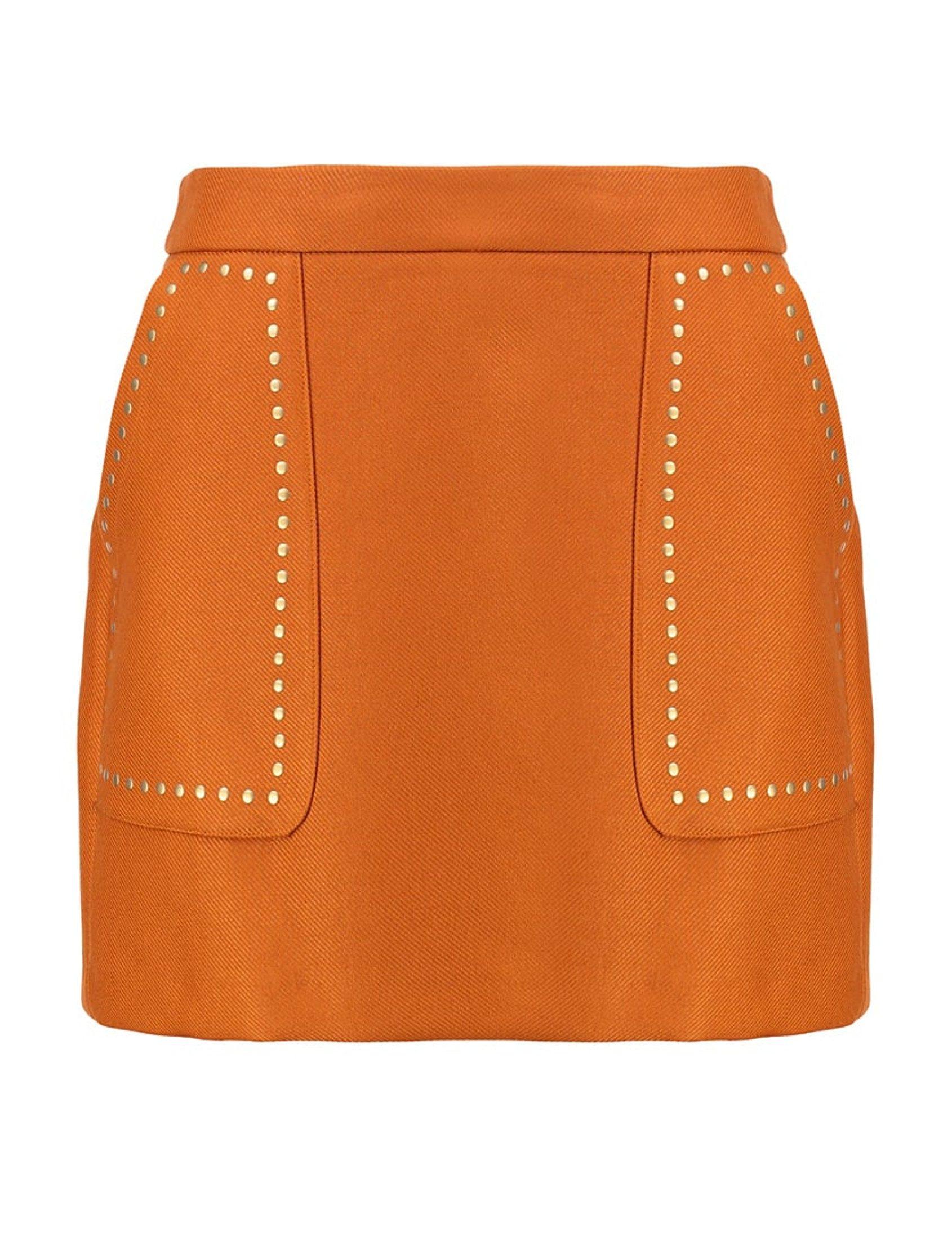 Esta falda de suave paño es la prenda ideal con un precioso color cognac, y bolsillos delanteros enmarcados en tachuelas planas de color oro mate.