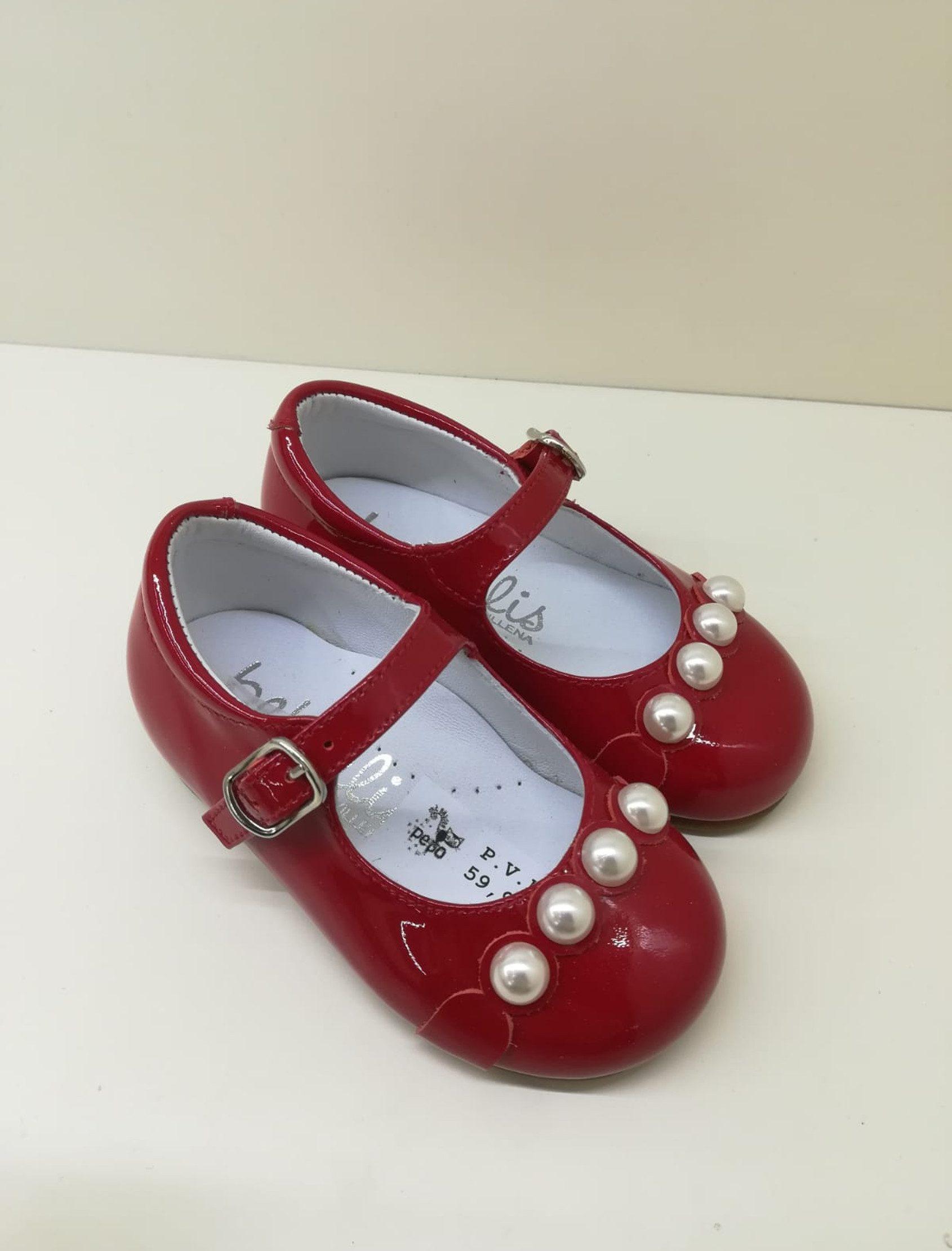Mercedes en charol rojo con tira de perlas blancas en la puntera a modo de adorno.