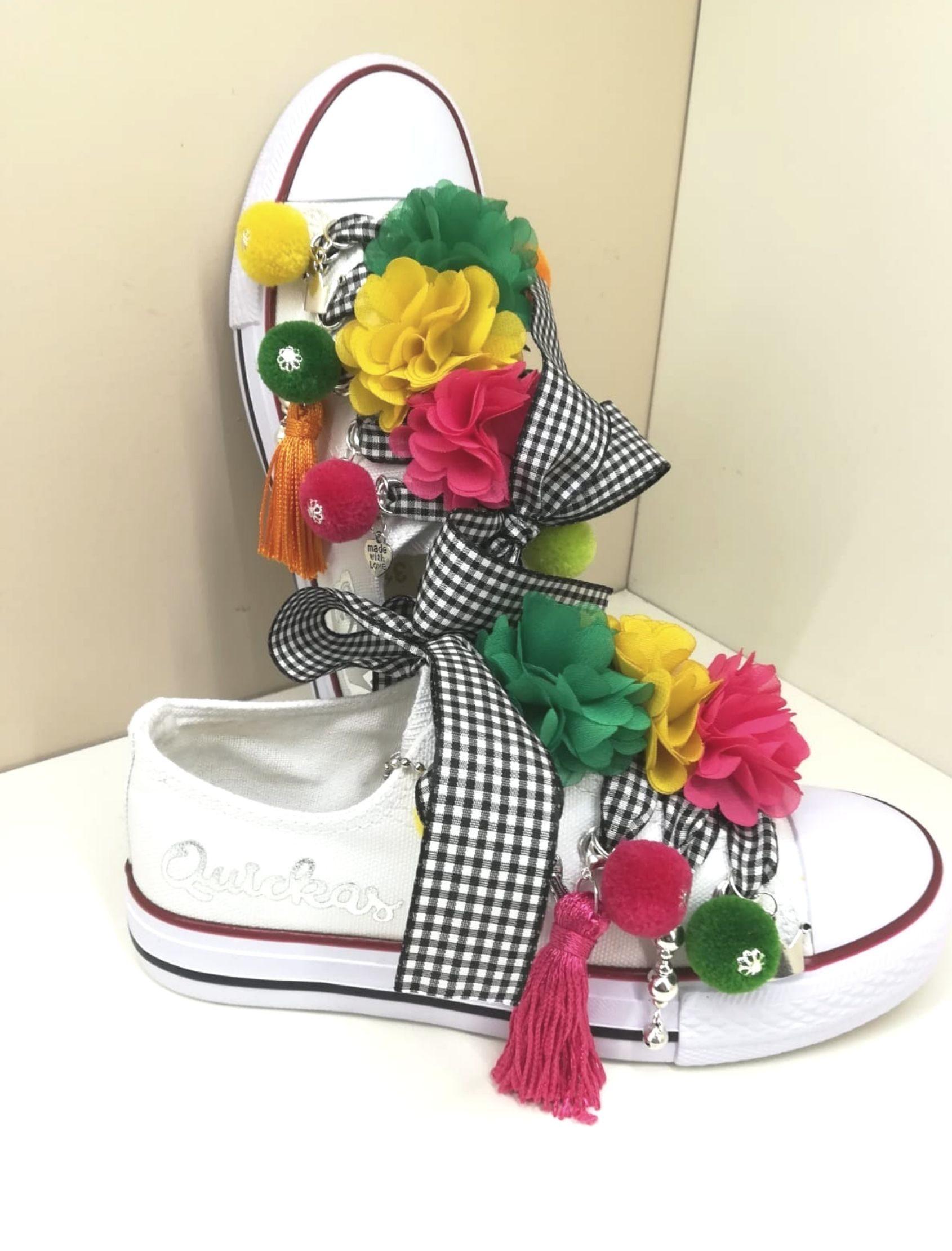 sneakers multicolor de la marca quickas con fondo blanco y pompones multicolor. Detalle de abalorios y cordones en cuadro vichy azul y blanco