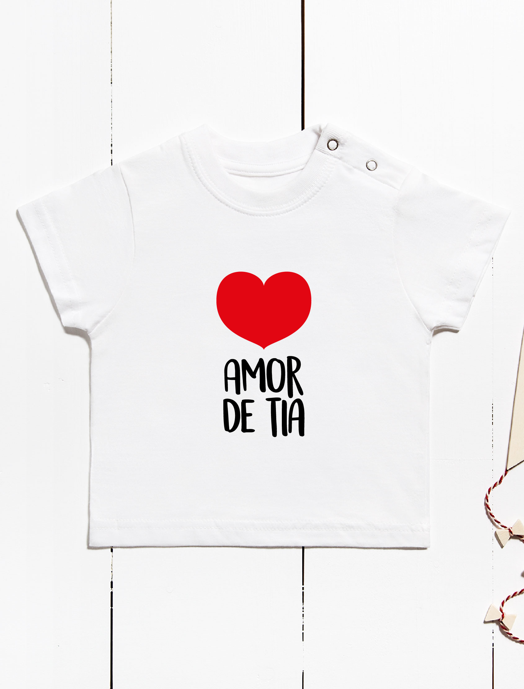 camiseta mc para bebés con manga corta y cierre de corchetes en hombro. Color blanco con mensaje amor de tia y corazón
