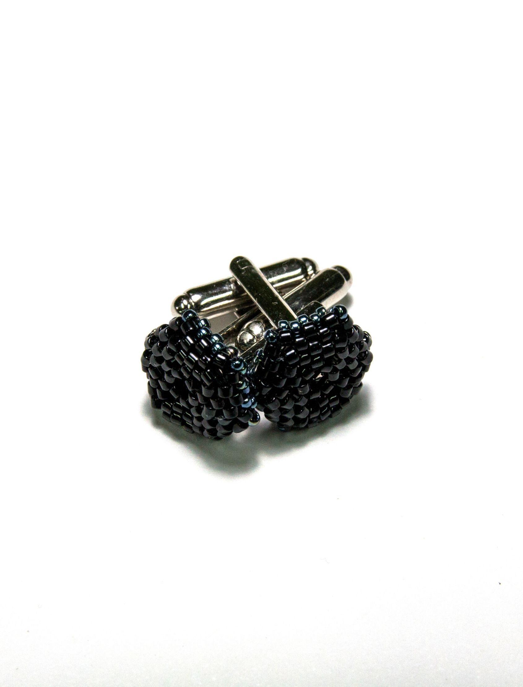 gemelos de acero negro con incrustaciones de la marca noso